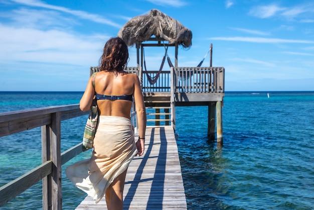 Een jonge vrouw in een bikini loopt naar een houten constructie van de caribische zee op roatan island. honduras