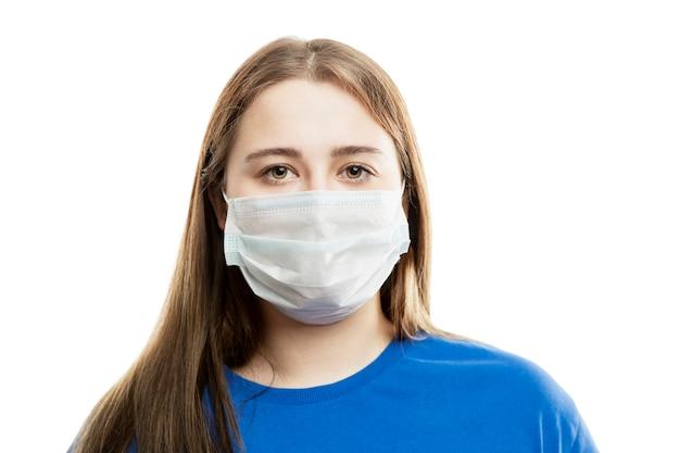 Een jonge vrouw in een blauw t-shirt met een medisch masker op haar gezicht