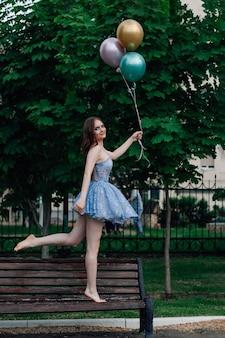 Een jonge vrouw in een blauwe jurk loopt blootsvoets op een houten bank en houdt vliegende ballonnen vast en doet alsof...