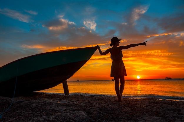 Een jonge vrouw in een boot bij roatan sunset vanuit west end. honduras