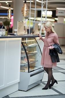 Een jonge vrouw in een café in een winkelcentrum, met een mobiele telefoon en met een papieren kopje koffie in haar hand.