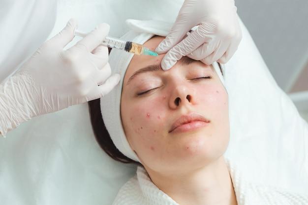 Een jonge vrouw in een cosmetologie-kliniek die een acnebehandeling ondergaat met injecties, een effectieve remedie