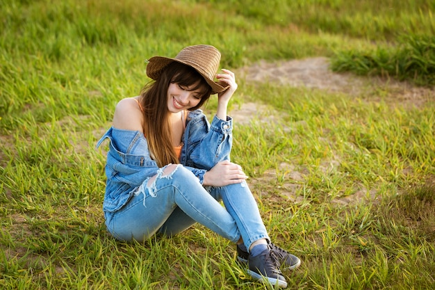 Een jonge vrouw in een denimkostuum en hoed, zittend op het gras