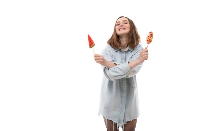 Een jonge vrouw in een denimoverhemd vormt met gekleurde lollies