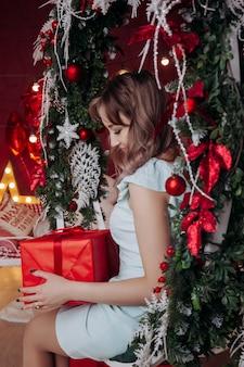 Een jonge vrouw in een feestelijke jurk zit op een decoratieve kerstschommel met een rode geschenkdoos