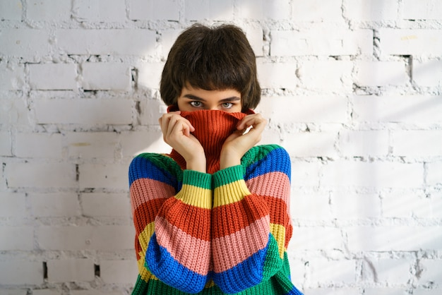 Een jonge vrouw in een felgekleurde regenboogtrui verbergt haar gezicht en bedekt haar oren met haar handen.