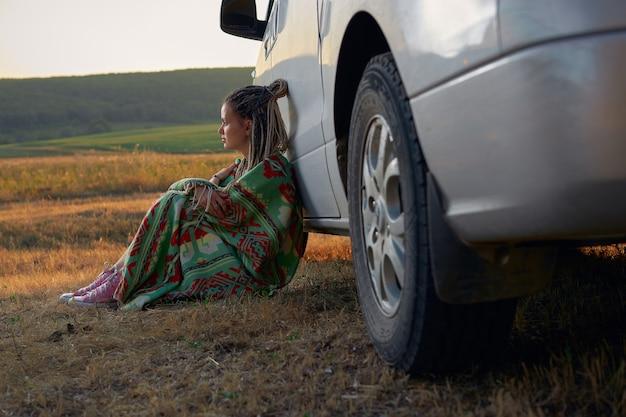 Een jonge vrouw in een felgroene deken zit leunend tegen een auto tegen de achtergrond van een groene...