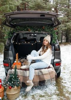 Een jonge vrouw in een gebreide muts zit in de kofferbak van een auto er zijn veel kerstcadeautjes