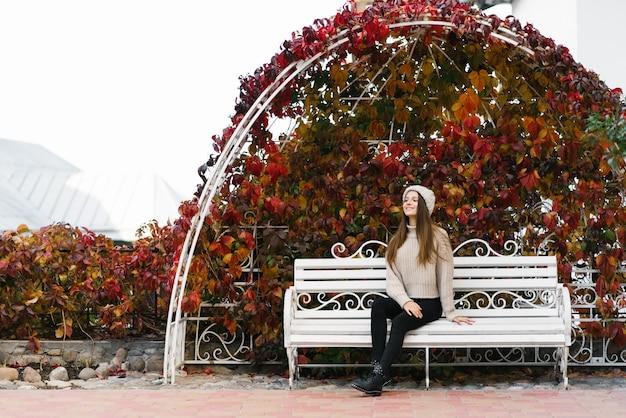 Een jonge vrouw in een gebreide trui en muts zit op een wit bankje in een herfstpark en dromen