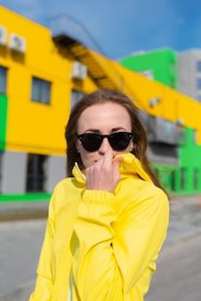 Een jonge vrouw in een gele jas en zonnebril met felle kleuren gebouwen op de achtergrond