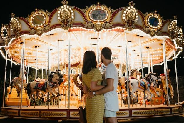 Een jonge vrouw in een gele jurk en haar vriendje met hun rug staren naar de carrousel. een paar geliefden op een date op de kermis in valencia.