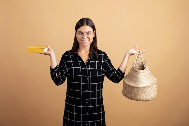 Een jonge vrouw in een geruite jurk staat met een rieten tas op een oranje achtergrond
