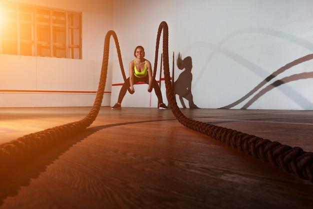 Een jonge vrouw in een groene sportbeha en een zwarte broek traint met touwen