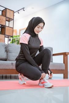 Een jonge vrouw in een hijab-trainingsoutfit gaat op haar hurken zitten terwijl ze haar schoenveters vastmaakt voordat ze binnenshuis traint
