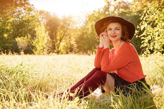 Een jonge vrouw in een hoed met een warme trui en een rok zit in het gras tegen de achtergrond van...