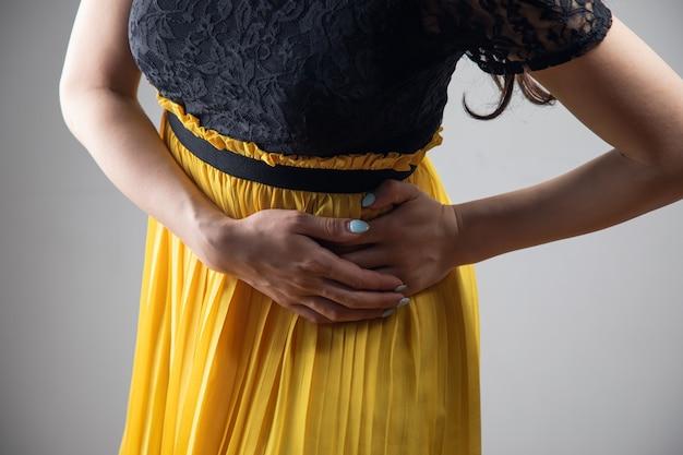 Een jonge vrouw in een jurk heeft een zere kant