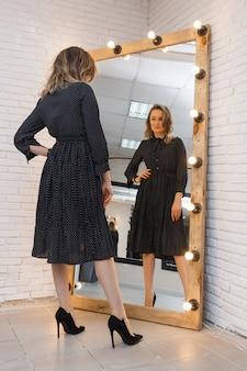 Een jonge vrouw in een jurk probeert een outfit die in een spiegel kijkt met gloeilampen in een kledingwinkel