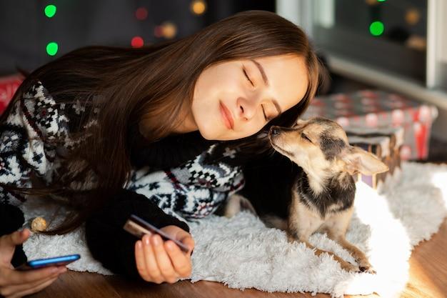 Een jonge vrouw in een kersttrui met een kleine hond knuffels