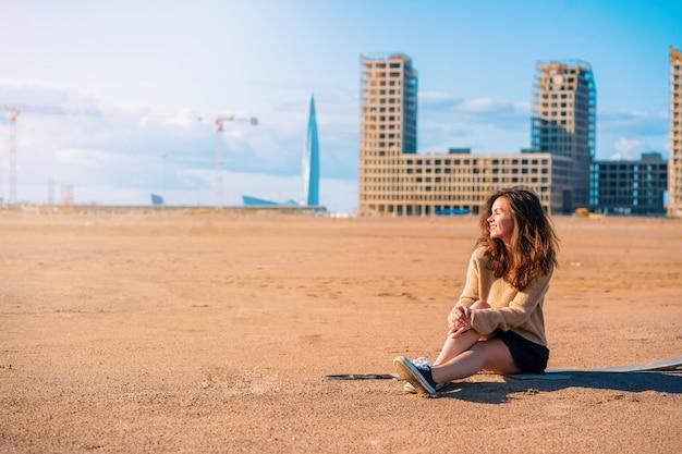 Een jonge vrouw in een knusse trui en rok zit op het zand, achter wolkenkrabbers in aanbouw