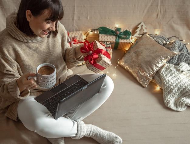 Een jonge vrouw in een knusse trui koopt kerstcadeautjes op internet. concept van het online kiezen van geschenken en het geven van afstand.