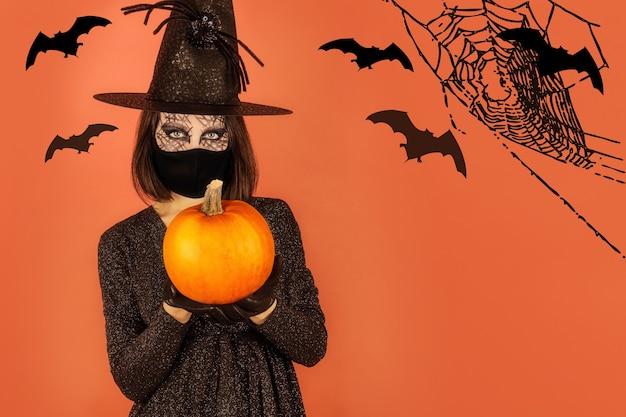 Een jonge vrouw in een kostuum en enge make-up met een lantaarnpompoen