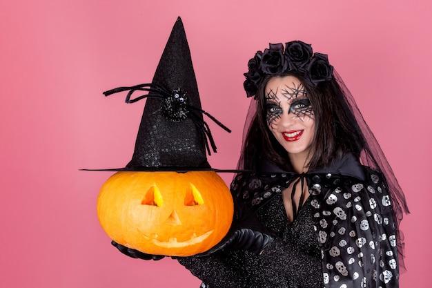 Een jonge vrouw in een kostuum en enge make-up met een pompoen in een heksenhoed