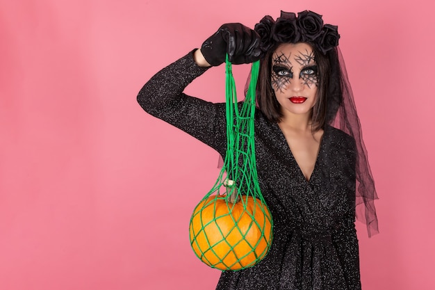 Een jonge vrouw in een kostuum voor halloween houdt een zak met een pompoen vast