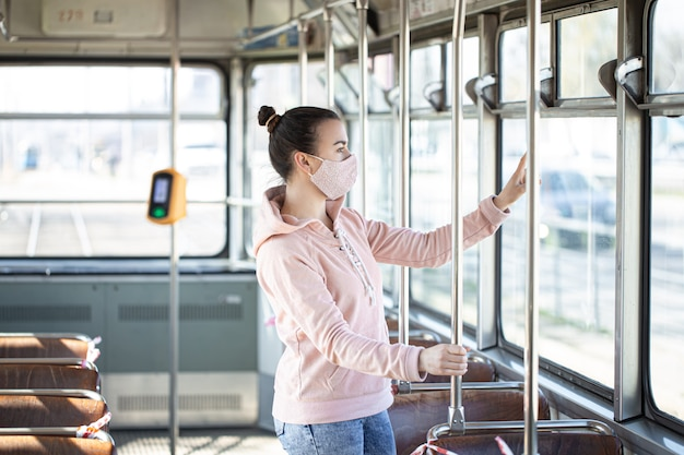 Een jonge vrouw in een leeg openbaar vervoer tijdens de pandemie. coronavirus.