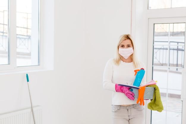 Een jonge vrouw in een masker en handschoenen heeft een spuitfles in haar handen. concept art voor het schoonmaken van ruimtes en het voorkomen van virale ziekten.