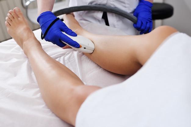 Een jonge vrouw in een moderne cosmetische kliniek over de procedure van laser ontharing van de benen