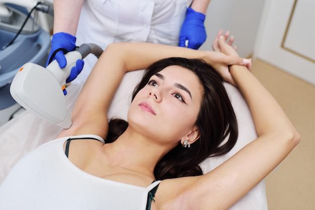 Een jonge vrouw in een moderne cosmetische kliniek over de procedure van laser ontharing van het okselgebied