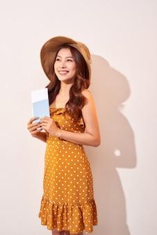 Een jonge vrouw in een oranje stippenjurk met een strohoed op haar hoofd houdt een paspoort en vliegtickets vast