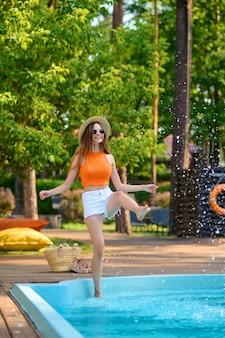 Een jonge vrouw in een oranje topje bij het zwembad