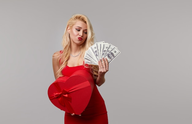 Een jonge vrouw in een rode jurk houdt in haar handen contant geld bankbiljetten, dollars en een hartvormige geschenkdoos. valentijnsdag en 8 maart