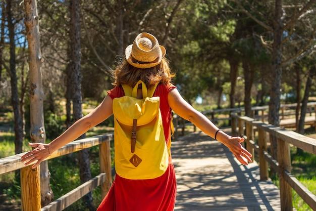 Een jonge vrouw in een rode jurk loopt langs de houten loopbrug naar moncayo beach in guardamar del segura, alicante