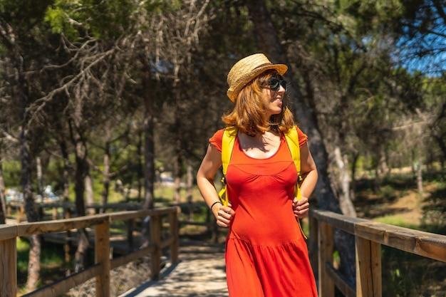 Een jonge vrouw in een rode jurk op het pad naar playa moncayo in guardamar del segura, alicante