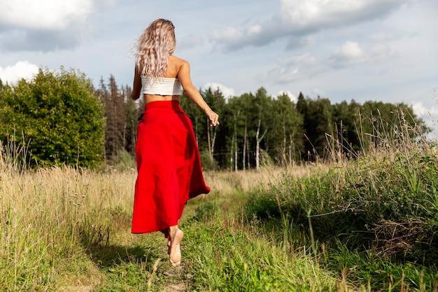 Een jonge vrouw in een rode rok rent in het veld