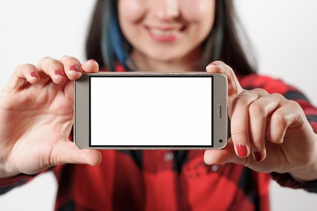 Een jonge vrouw in een rood en zwart shirt houdt een smartphone met een leeg wit scherm