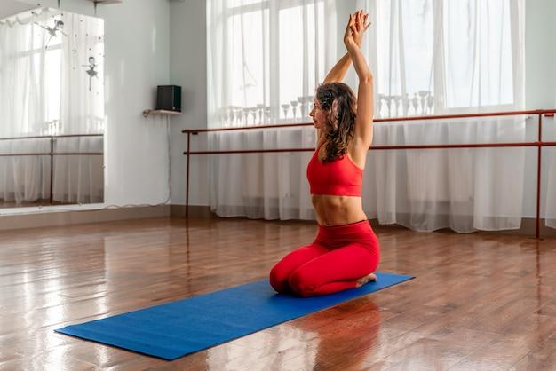 Een jonge vrouw in een rood trainingspak doet oefeningen of yoga in de sportschool.