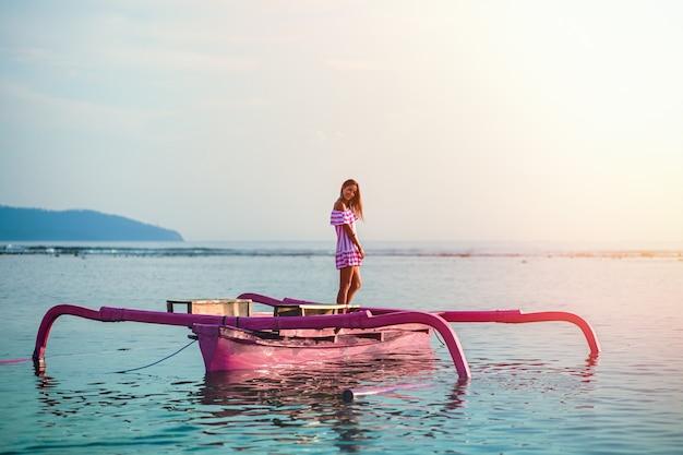 Een jonge vrouw in een roze zomerjurk staat in een roze boot op de blauwe zee.