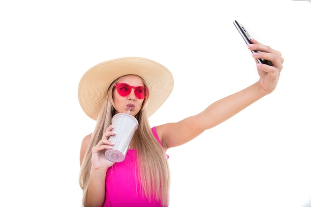Een jonge vrouw in een roze zwembroek en hoed die een glas houdt en een selfie neemt. geïsoleerd