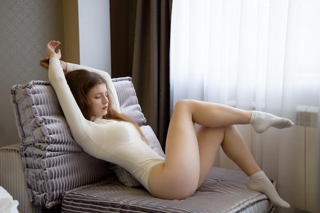 Een jonge vrouw in een sexy bodysuit zit op een grote stoel met haar benen over elkaar en haar ogen dromerig gesloten