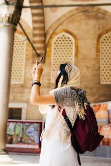 Een jonge vrouw in een sjaal maakt foto's op de binnenplaats van de moskee aan de telefoon