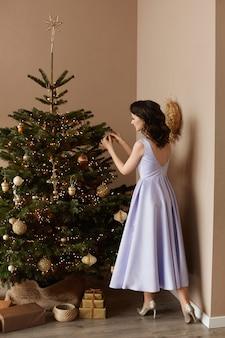 Een jonge vrouw in een stijlvolle avondjurk die een kerstboom in de woonkamer versieren