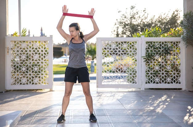 Een jonge vrouw in een tanktop en korte broek gaat sporten met een expander in de open lucht.