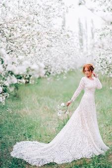 Een jonge vrouw in een trouwjurk staat in een bloeiende lentetuin