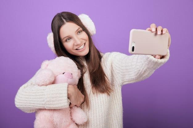 Een jonge vrouw in een trui en roze oren neemt een selfie en knuffels met speelgoed.