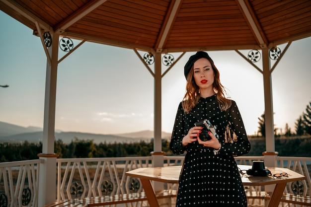 Een jonge vrouw in een vintage zwarte polka-dot jurk met een oude camera in haar handen die zich voordeed op straat