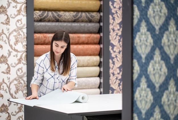 Een jonge vrouw in een winkel kiest wallpaper voor haar huis. concept van reparatie en winkelen.