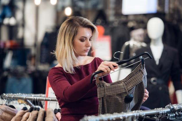 Een jonge vrouw in een winkelcentrum, het kopen van kleding